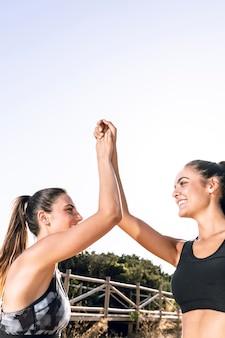 Amici a fare jogging facendo il cinque