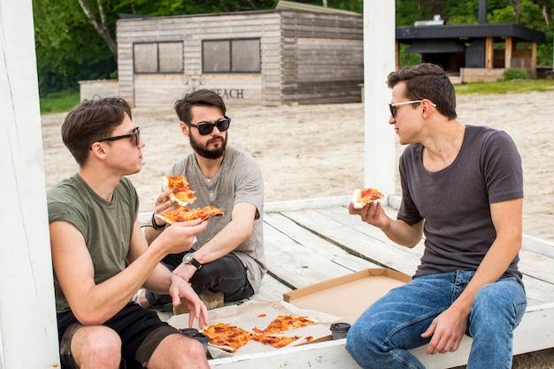 Amici a parlare e mangiare la pizza sulla spiaggia