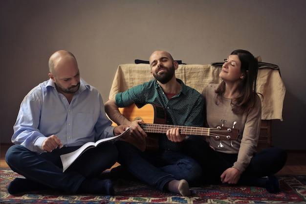 Amici adulti che si godono una pratica di chitarra