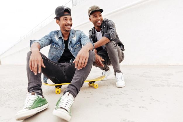 Amici africani degli uomini che camminano all'aperto che si siede con il pattino