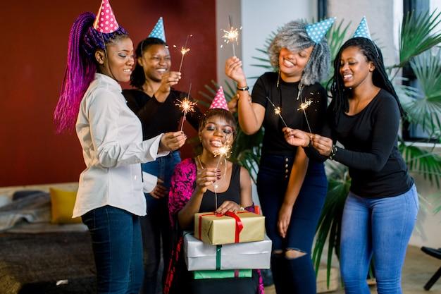 Amici africani festeggiano il compleanno e tengono le luci del bengala e con cappelli e regali