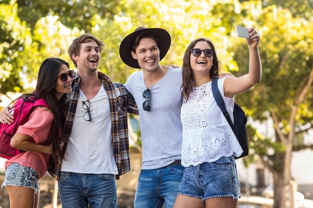 Amici alla moda che fanno selfie per le strade