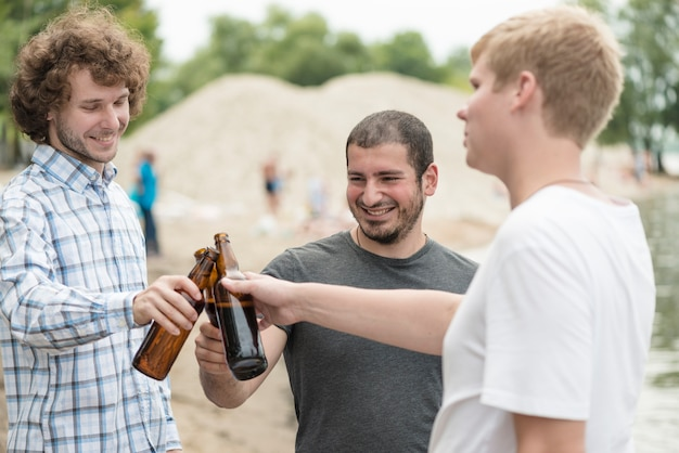 Amici allegri che clinking le bottiglie sulla spiaggia