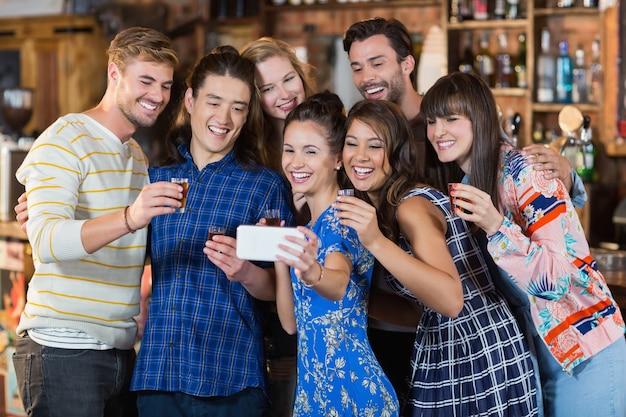 Amici allegri che prendono selfie tenendo gli occhiali corti