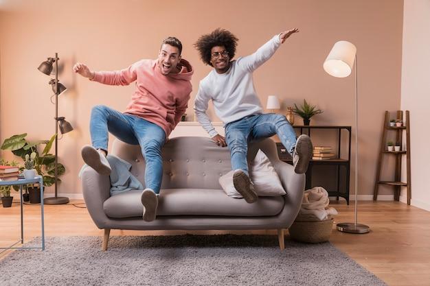 Amici allegri che saltano sul divano