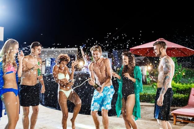 Amici allegri che sorridono, rallegrandosi, riposando alla festa vicino alla piscina
