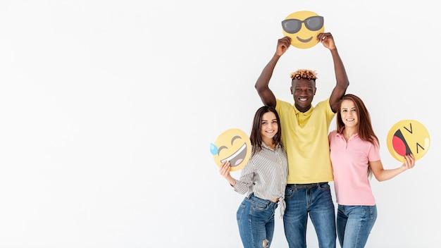 Amici allegri che tengono emoji copia-spazio