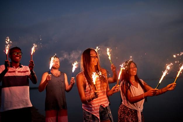 Amici allegri con le stelle filanti sulla spiaggia di estate