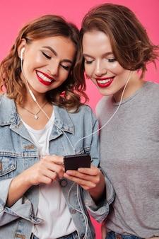 Amici allegri delle donne che usando musica d'ascolto del telefono cellulare.