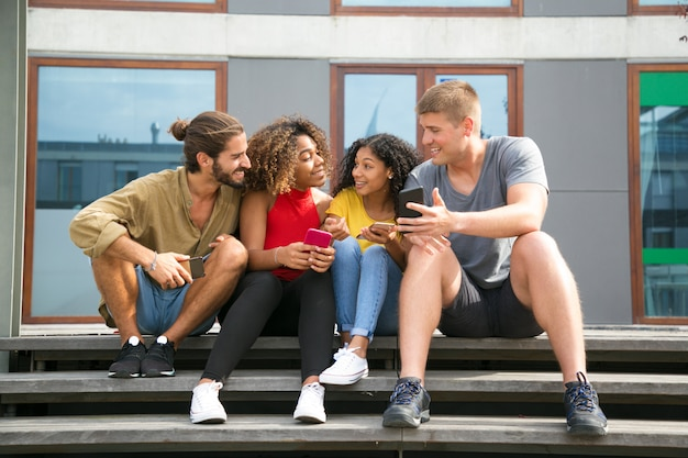 Amici allegri felici che leggono le notizie sugli schermi del telefono
