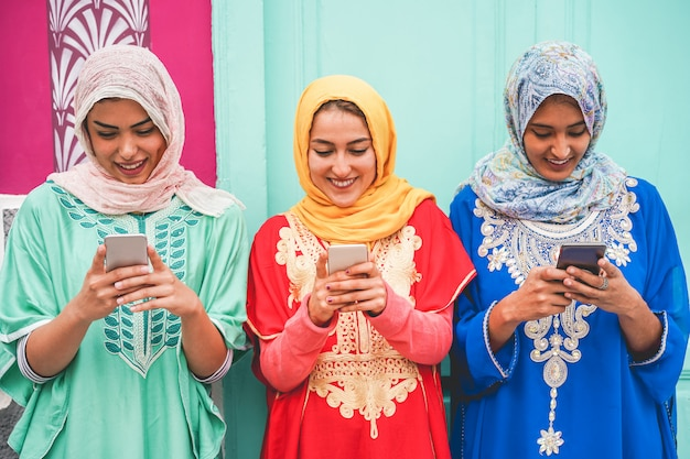 Amici arabi felici utilizzando gli smartphone all'aperto - giovani ragazze islamiche che si divertono con la nuova tecnologia di tendenza - influencer e concetto di amicizia - focus sui volti