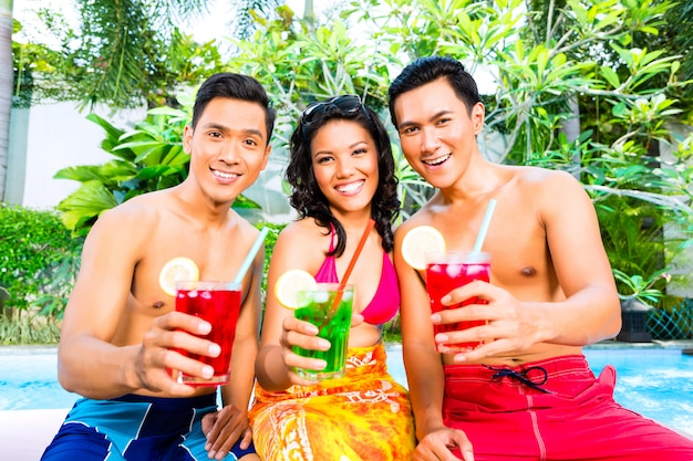 Amici asiatici bevendo cocktail in piscina
