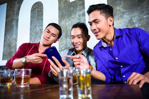 Amici asiatici che bevono colpi in discoteca