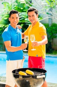 Amici asiatici che hanno barbecue che beve vino bianco