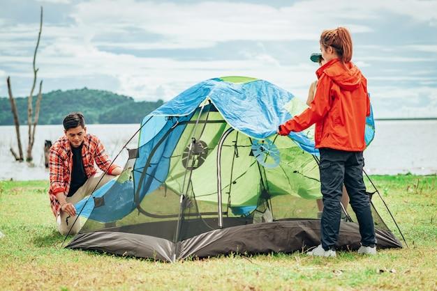 Amici asiatici che installano la tenda all'aperto sul lago