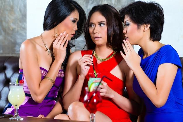 Amici asiatici spettegolare in discoteca
