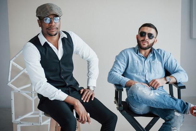 Amici barbuti in posa con gli occhiali da sole sulla sedia