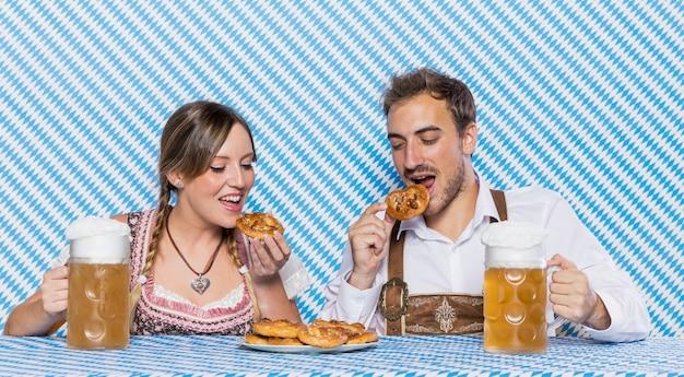 Amici bavaresi che assaggiano gli spuntini più oktoberfest