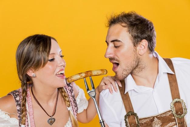 Amici bavaresi che assaggiano la salsiccia deliziosa