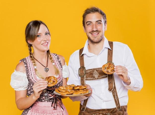 Amici bavaresi felici che tengono le ciambelline salate