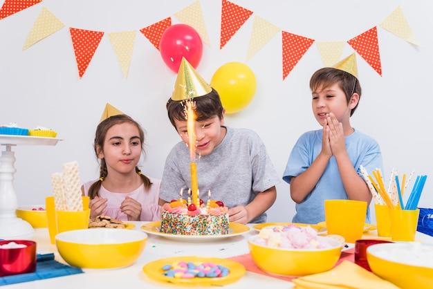 Amici che applaudono mentre ragazzo che taglia la sua torta di compleanno a casa