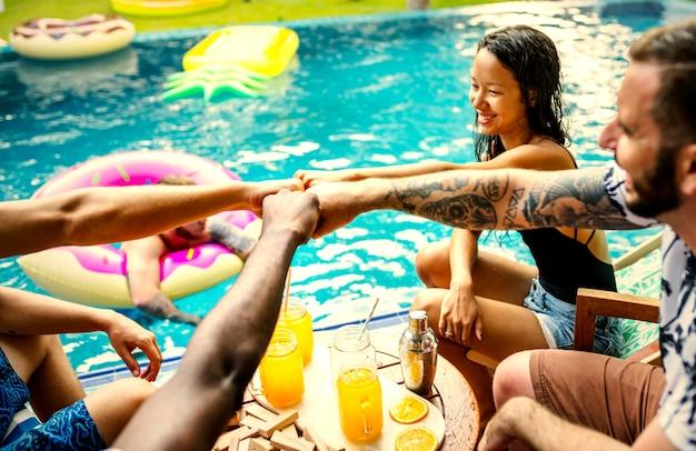 Amici che bevono bevande colorate a una festa in piscina