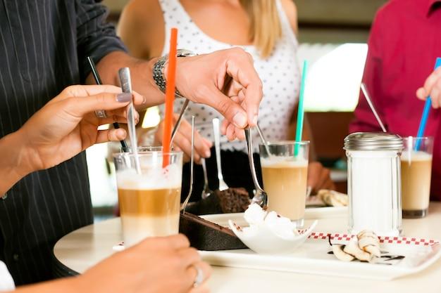 Amici che bevono caffè al latte e che mangiano torta