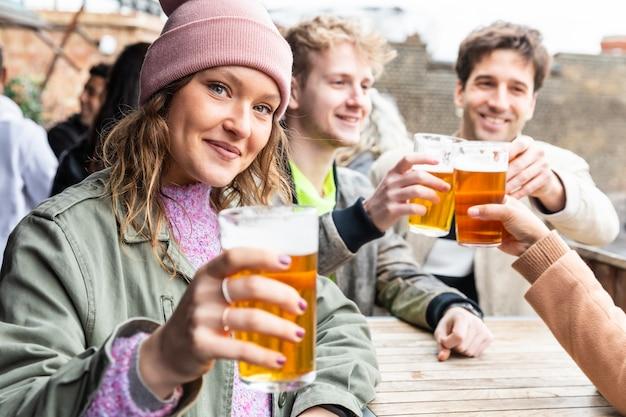 Amici che bevono e che tostano con la birra al pub