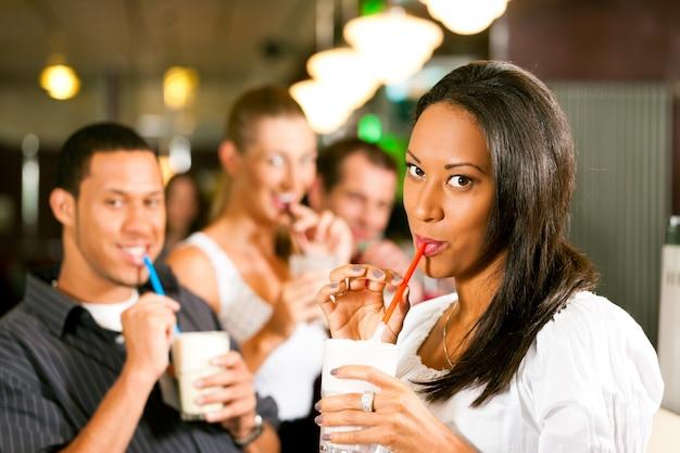 Amici che bevono frappè in una barra