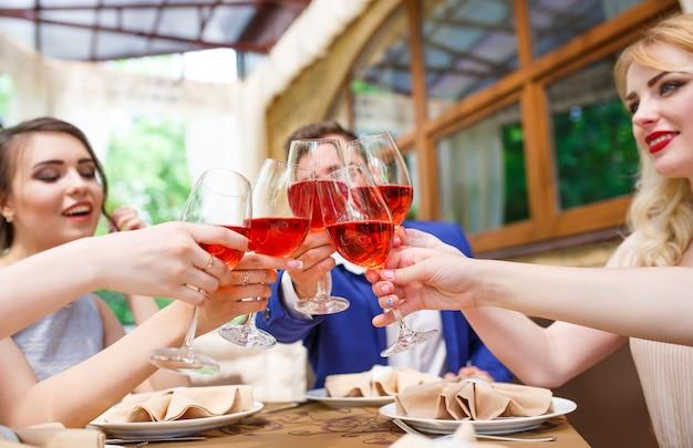 Amici che bevono vino sulla terrazza estiva.