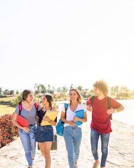 Amici che camminano da studi in giornata di sole