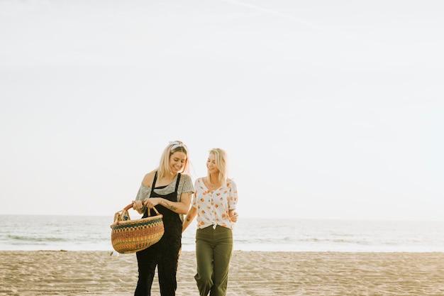 Amici che camminano sulla spiaggia con un cestino da picnic