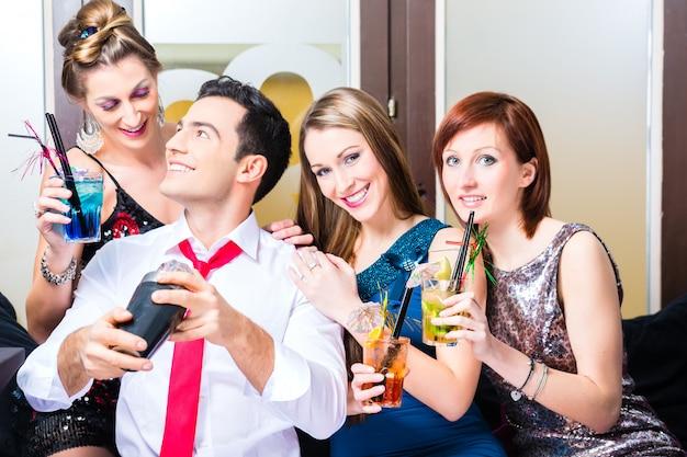 Amici che celebrano con barista nel cocktail bar