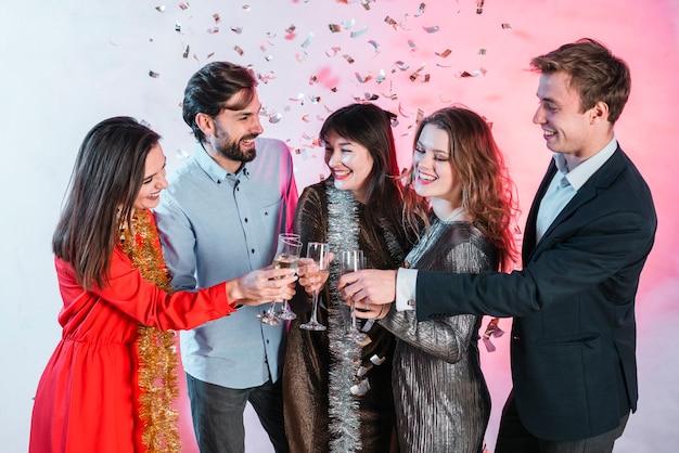 Amici che celebrano il natale e bicchieri di champagne tintinnanti