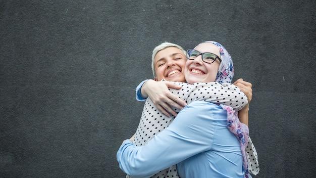 Amici che condividono un abbraccio con sfondo nero