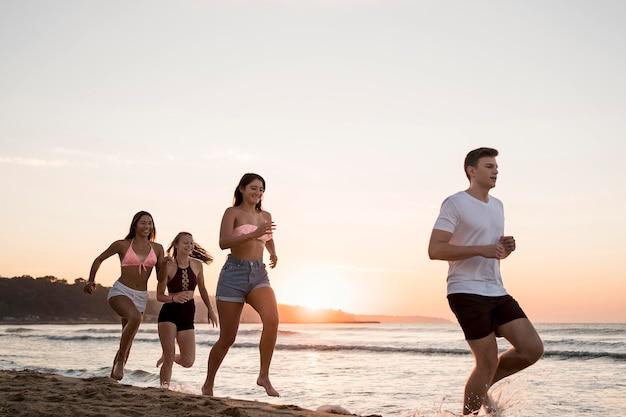 Amici che corrono insieme sulla spiaggia