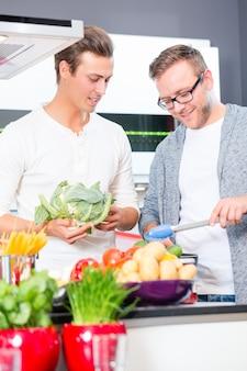 Amici che cucinano vegies e carne in cucina domestica