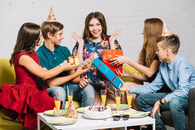 Amici che danno scatole regalo avvolte alla ragazza eccitata del compleanno