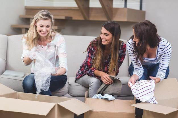 Amici che disimballano le scatole di cartone