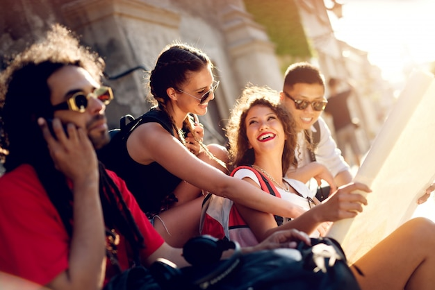 Amici che esplorano la fortezza della città vecchia. divertirsi in strada. seduto sulle scale.