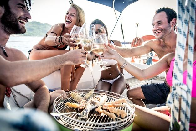Amici che fanno il pesce barbecue sull'yacht