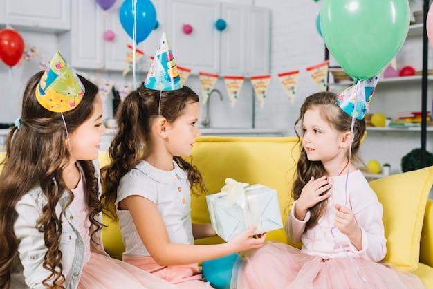 Amici che fanno regali al loro amico durante il compleanno