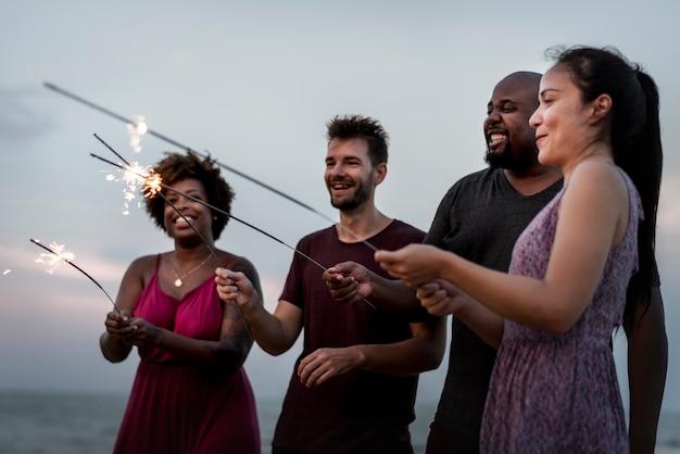 Amici che festeggiano con stelle filanti in spiaggia