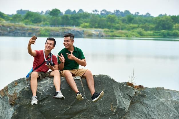 Amici che fotografano sulla roccia