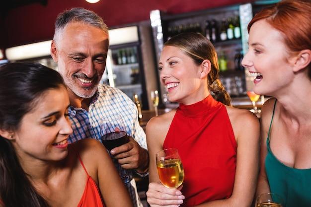 Amici che godono del vino in discoteca