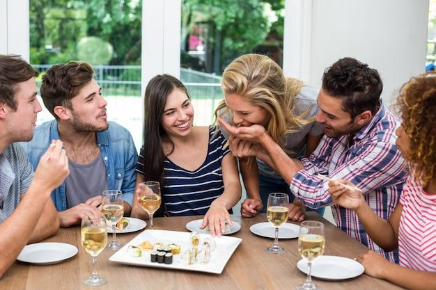 Amici che godono di vino e sushi a casa