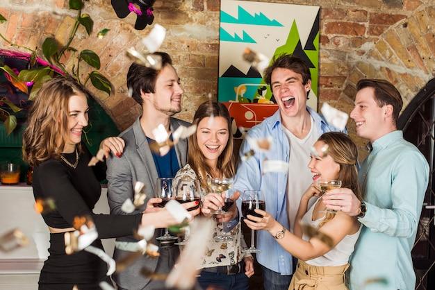 Amici che godono la festa con la tostatura del bicchiere di vino