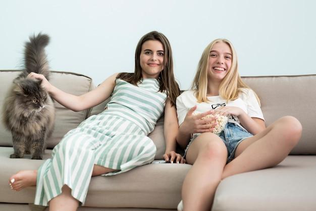 Amici che guardano un film con il gatto birichino