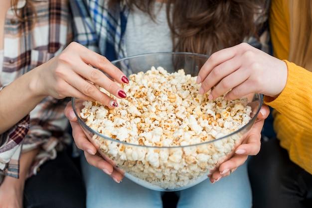 Amici che guardano un film mentre mangiano popcorn