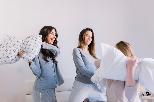 Amici che hanno lotta con i cuscini
